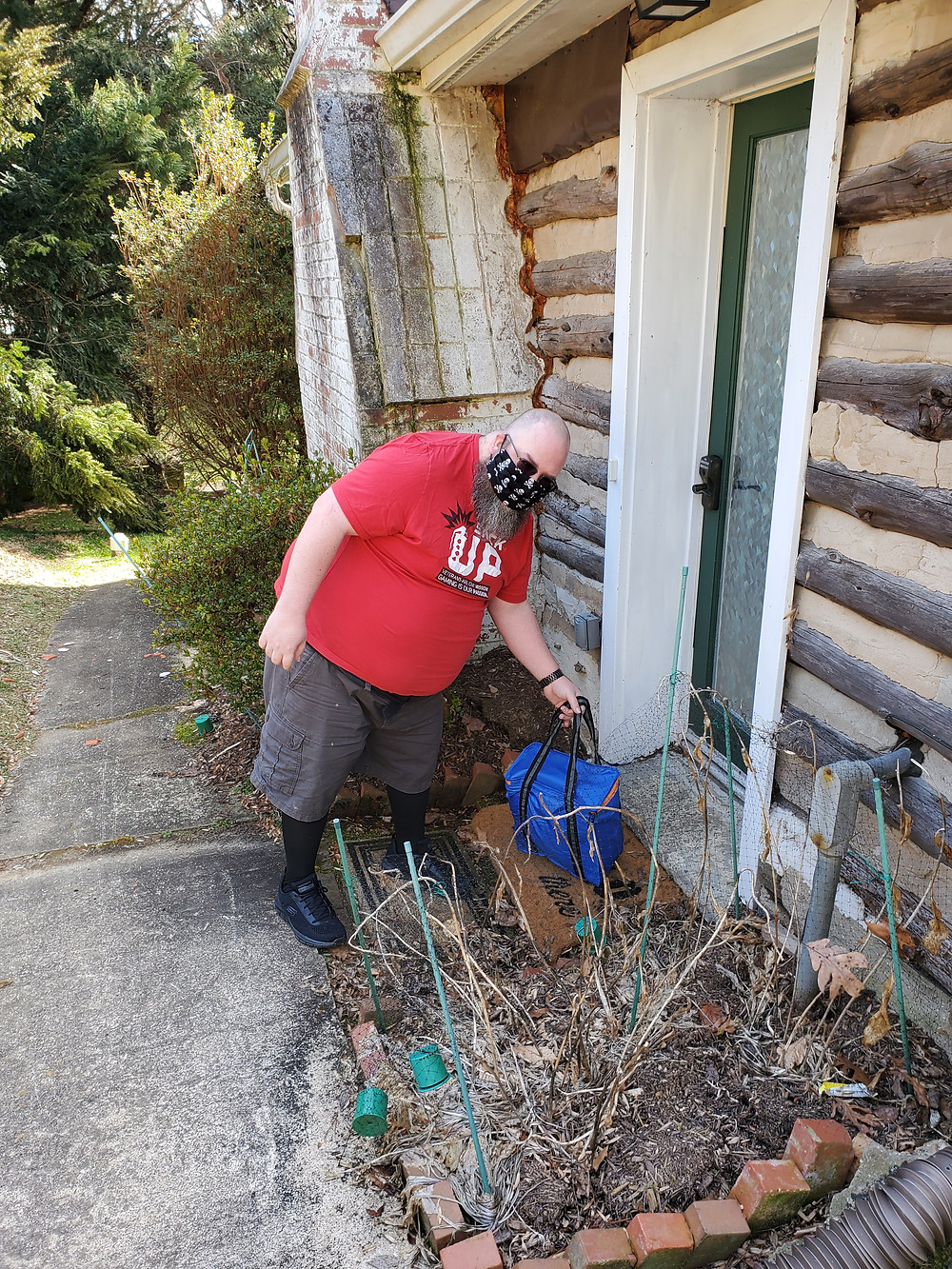 A stack up member delivers meals on wheels to a home. He is wearing his stack up t shirt.
