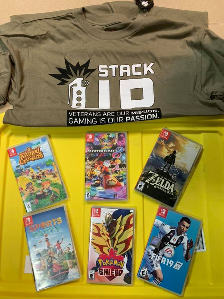 A Stack Up T-shirt in Army green sits on the yellow lid of the Supply Crate. with 6 Nintendo Switch video games below it. The games are Animal Crossing, Mario Kart 8, Legend of Zelda: Breath of the WIld, Sports Party, Pokemon Shield, and Fifa 19.