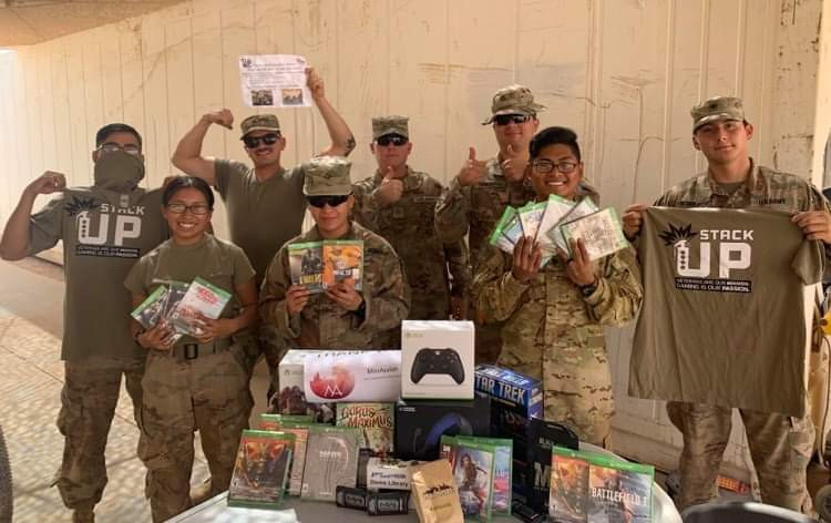8 soldiers hold up various video games and Stack Up t-shirts. They are smiling.