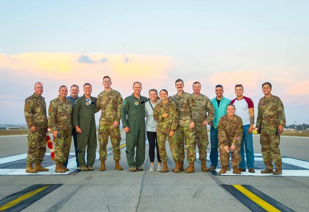 14 airmen stand on a runway. Some are in military uniform. Some are in normal clothing.