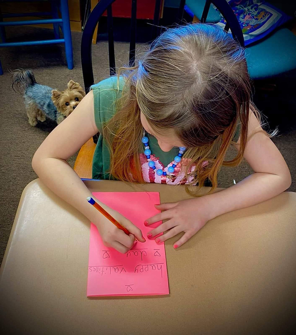 A girl makes a valentines card.