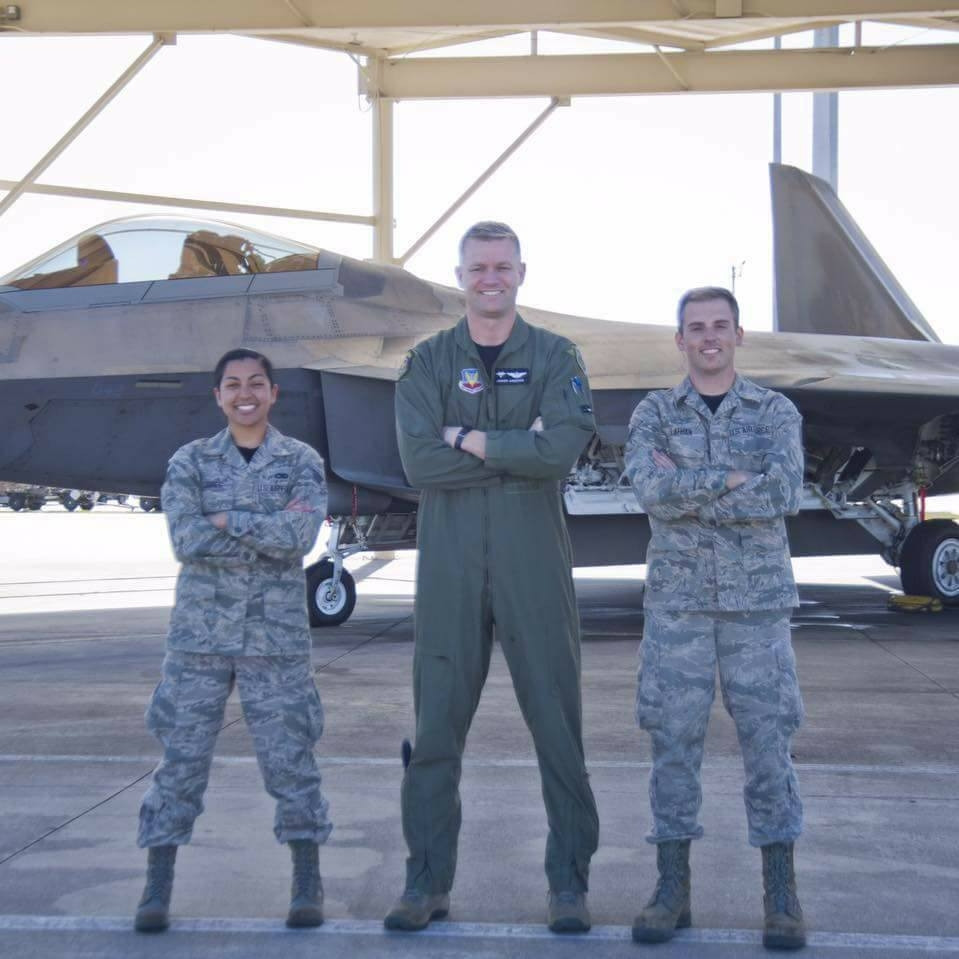 3 airmen pose in military uniform in front of a jet. They're all smiling.