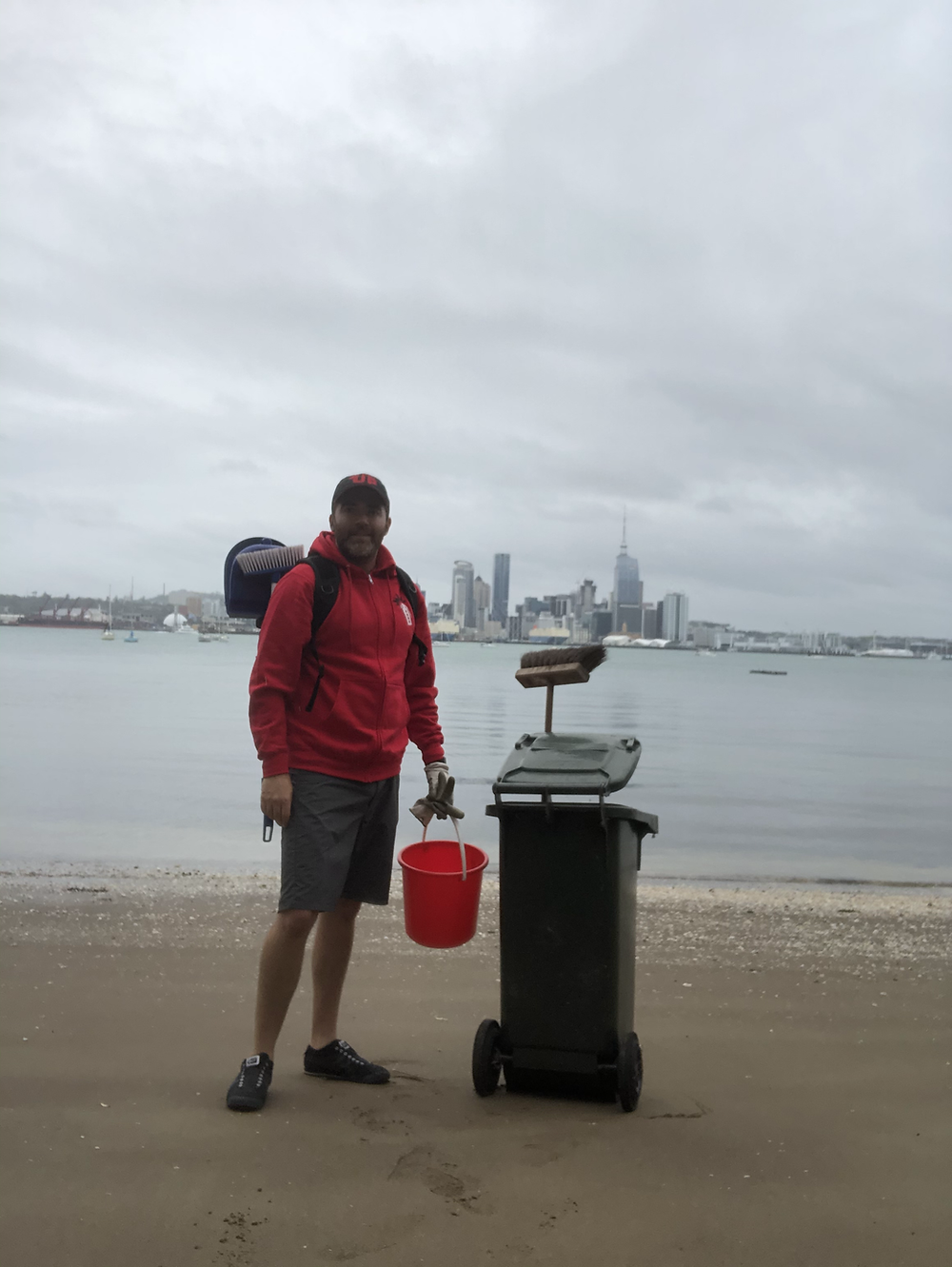 Aston, the single Stack member in New Zealand stands by a trash can on the beach. He is happy with his cleanup.