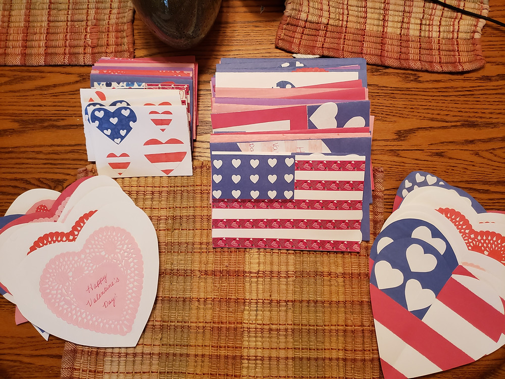 At least 50 valentines cards are stacked together. They all have American flags with hearts.