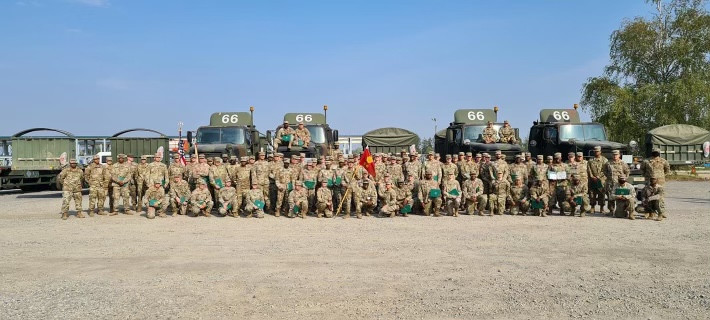Picture of about 40 soldiers all in uniform. Matthew's 88M unit all standing in front of the military transports that they drive.