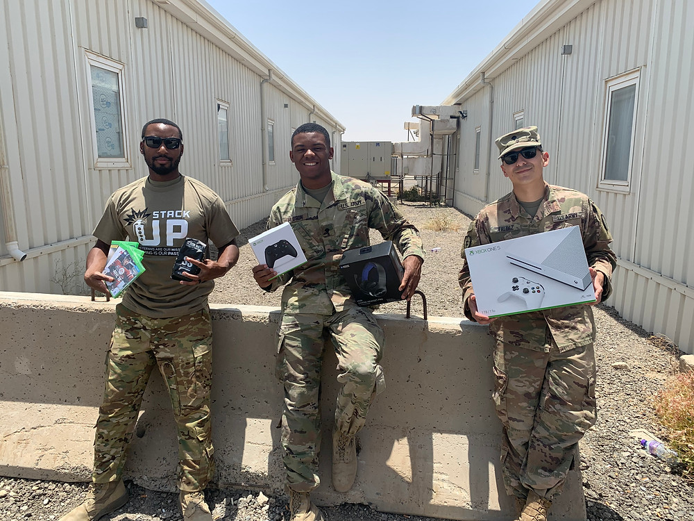 3 soldiers lean against a concrete barrier. From left to right: The left soldier holds up a couple of xbox games and an xbox controller. The soldier in the middle holds up an xbox controller still in the box and gaming headphones. The soldier on the right holds up an Xbox One S console box.