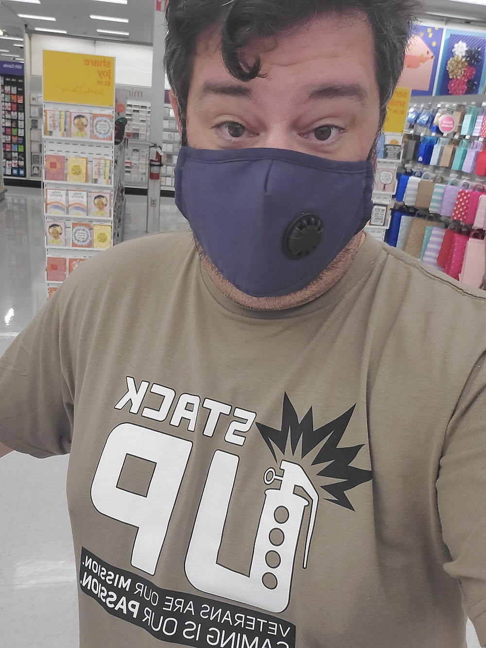 Selfie: Giles wears a mask and Stack Up shirt. He is at the store.