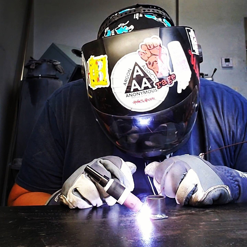 Jonathan is wearing a welding helmet and welding gloves while he welds pieces of metal together. He has a bunch of stickers all over the welding helmet. Including Spongebob, a sticker that says Rage and another that says Argon Addicts Anonymous.
