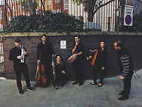 Riot Ensemble members in the City of London, making noise next to a keep noise down sign
