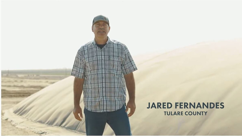 A California dairy farmer standing by an anaerobic digester that creates carbon-negative transportation fuel.