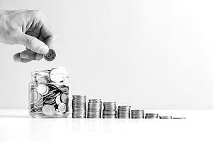 person-s-hand-putting-money-glass-jar-ne