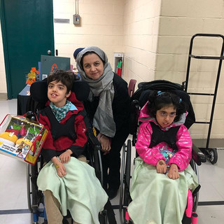 A woman in a headscarf smiles next to two children who are sitting in wheelchairs.