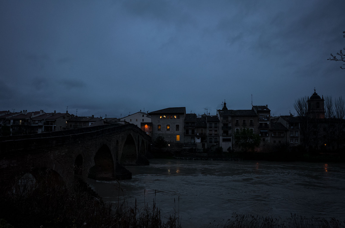 The lights of an albergue are the only sign of predawn life in Puente la Reina.