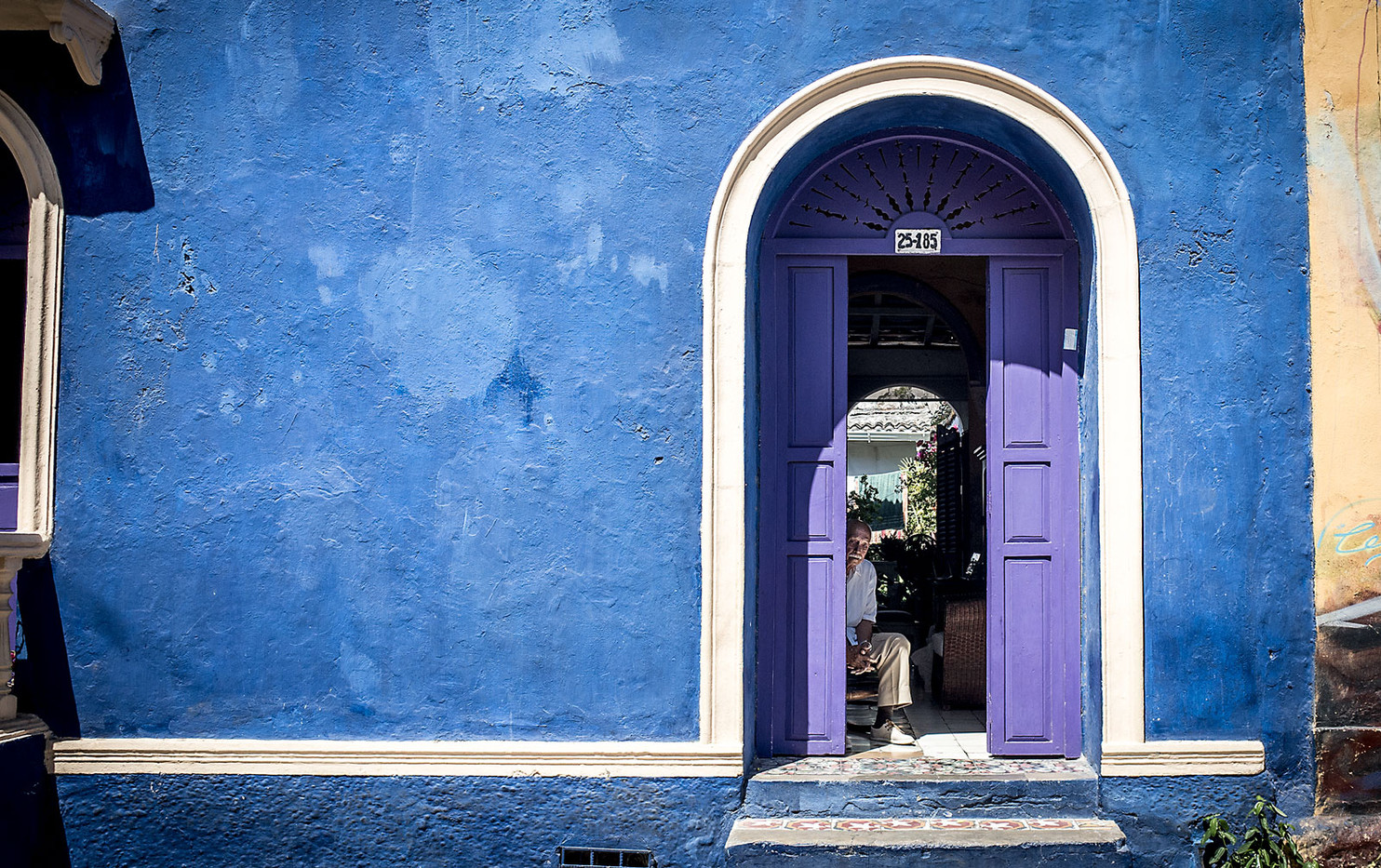 A man keeps cool in the shade of his doorway near Plaza de la Trinidad, Cartagena.