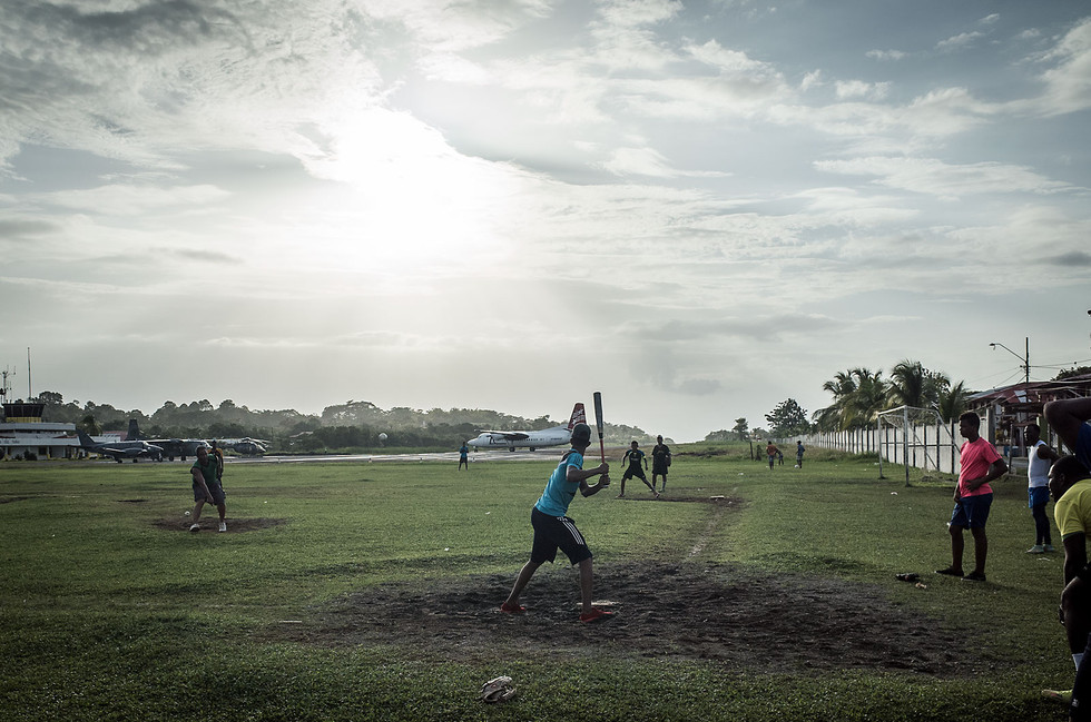 Men play a pickup game of baseball in an adjacent field to the airport in Bocas town, Panama.