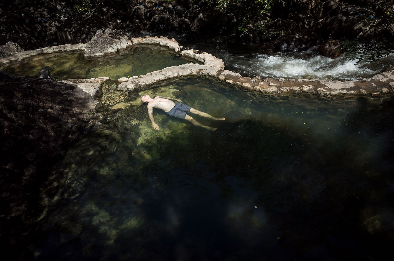 A traveler relaxes in a volcanic hot spring pool near Rincón de la Vieja park, Costa Rica.