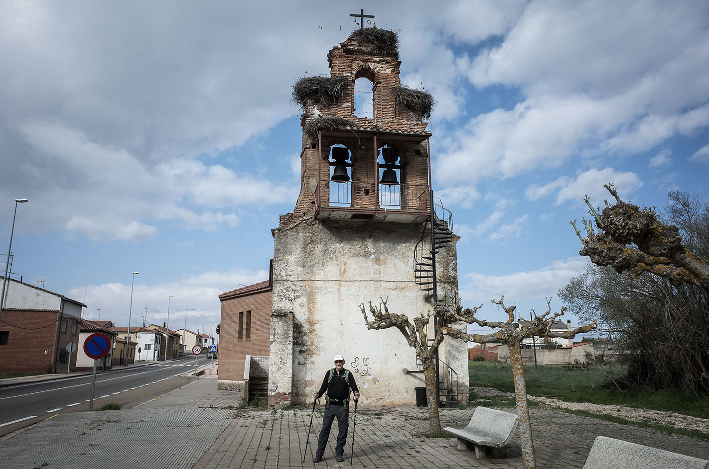 Don (United States) is recently retired and decided to walk the Camino for both health and spiritual reasons. He turned 76 two days after reaching Santiago de Compostela.  In the background are the remains of a church crowned with three enormous stork nests. The nests are a common sight atop bell towers and chapels along the central part of the Camino, as are the storks who fly about gathering dunnage.