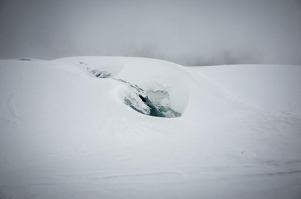 A crevasse appears like a hidden ice cave amid a snowy glacial surface.