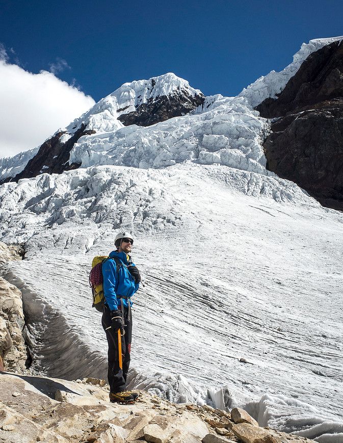 Gus, a Norwegian climber, pauses to find the fastest route across a glacial col to limit his time below the seracs above on Nevado San Juan.