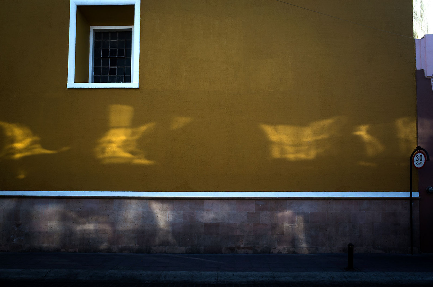 Reflected sunlight patterns decorate a wall in León.