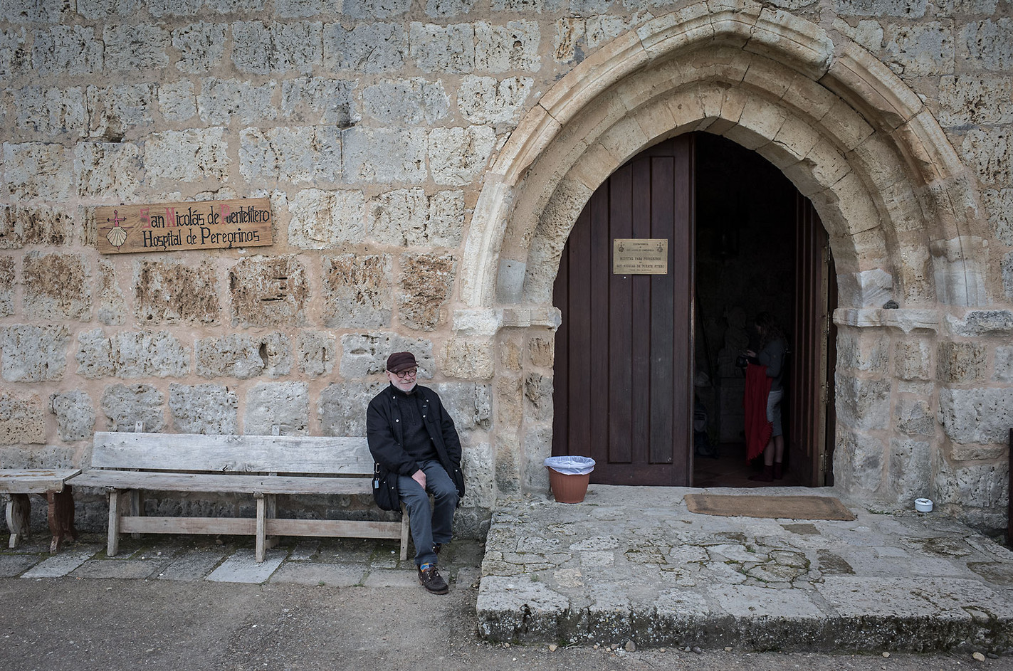 The San Nicolas Pilgrim's Hostel in Itero del Castillo is run by Italians from the Confraternity of San Jacopo di Compostella near Perugia. The hostel is in a small monastery restored 30 years ago by the Confraternity. Here the hospitalero sits outside to have a cigarette break. Centuries ago the monks here would wash the feet of pilgrims staying overnight at the monastery. Today, the Italian hosts keep up the tradition with a symbolic washing of the feet (water is poured over one foot of each guest). A full Italian meal is then served amid candle light, as the building has no electricity.