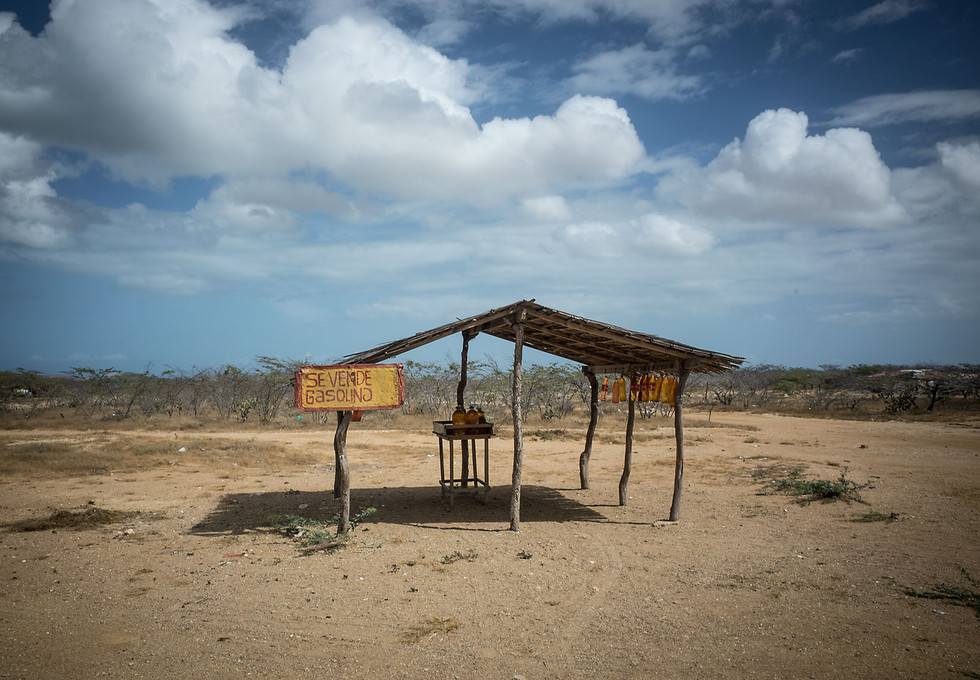 A local gas vendor in the desert coast of La Guajira. Gas stations are rare past Uribia, so fuel tank calculations are important when leaving the asphalt. Luckily, locals repurpose plastic bottles as fuel containers, which they sell to desperate motorists.
