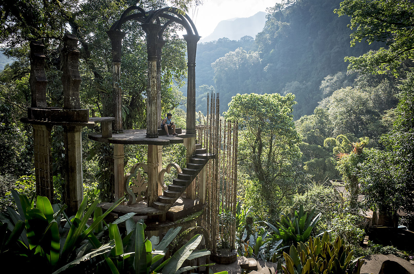 A visitor to Las Pozas in Xilitla waits atop a surrealist structure while his friends take a picture. The park was the vision of British poet Edward James, who was deeply interested in surrealism. The park was purchased from the James estate by a foundation which now overseas the 80 acres of natural waterfalls and concrete structures.