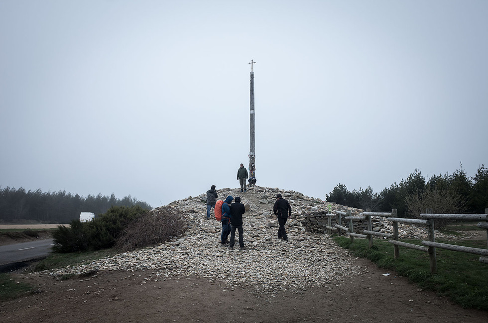 "The Cruz del Hierro represents the highest point on the Camino Frances. It is tradition for pilgrims to carry a small stone representing a emotional or spiritual burden in the pack. Upon reaching the Cruz, pilgrims deposit the stone and ""unburden"" themselves."