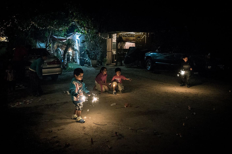 Children light fireworks as part of Christmas Eve celebrations in Panajachel.