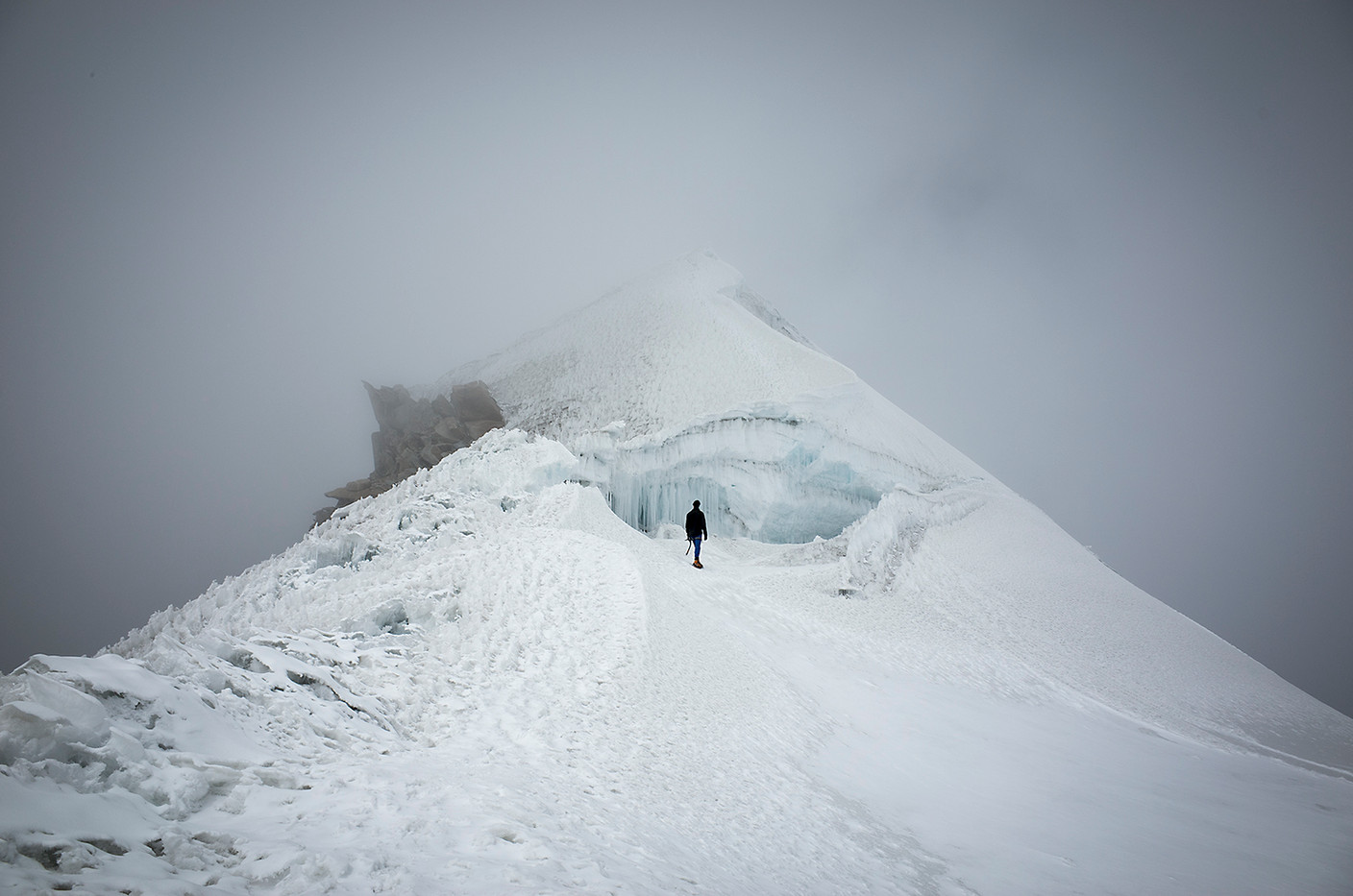 A climber stares into the gaping maw of a minor peak before ascending.