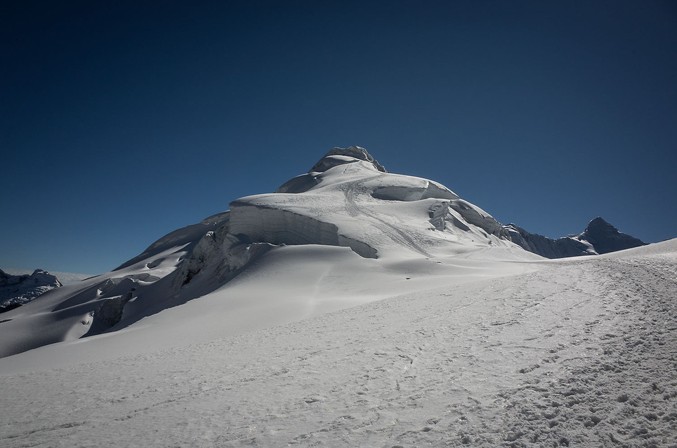 The summit pyramid of Ishinca resembles a whipped sundae topping when seen from the col on the southwest ridge.