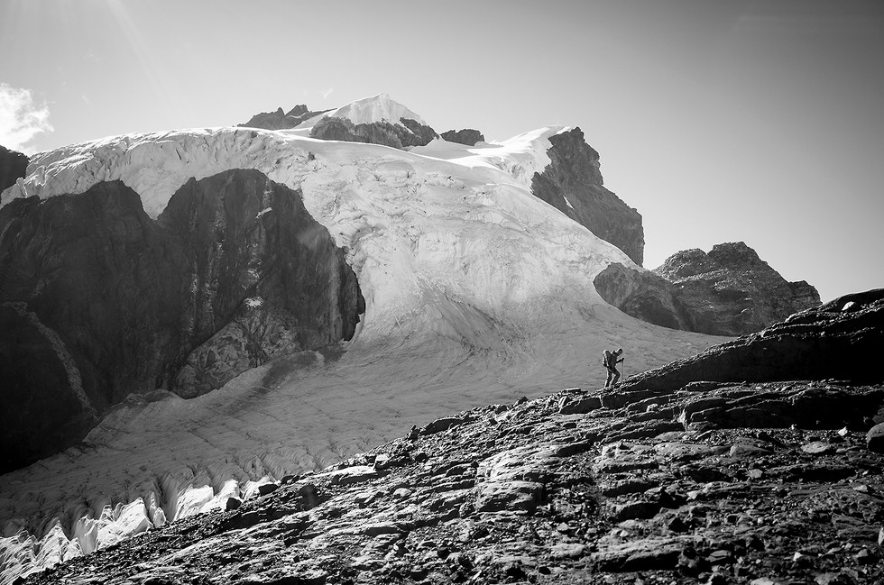 Maparaju's west face looms large in the distance behind a climber.