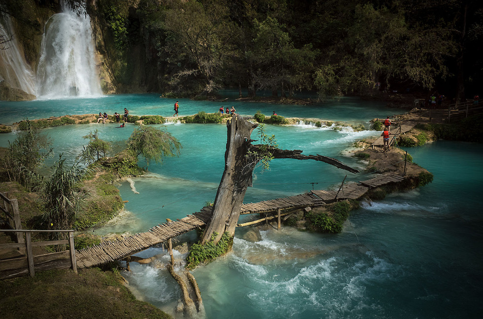 Vacationers play in the various pools formed by the Minas Viejas waterfalls in Huasteca region of San Luis Potosi. The blue water is due to high levels of travertine, a type of limestone.