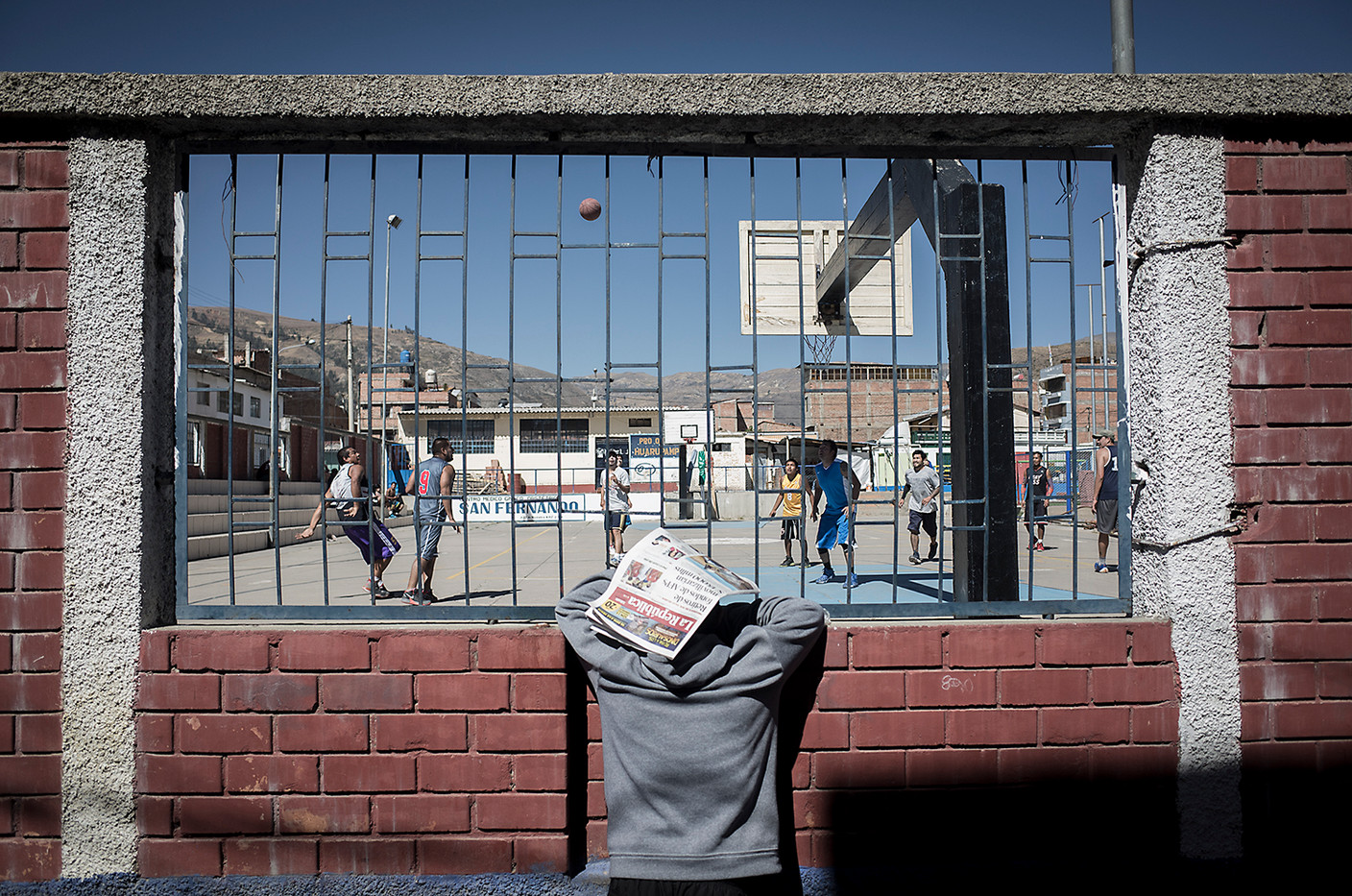 A spectator shields himself from the midday sun while watching a pickup game in Huaraz.