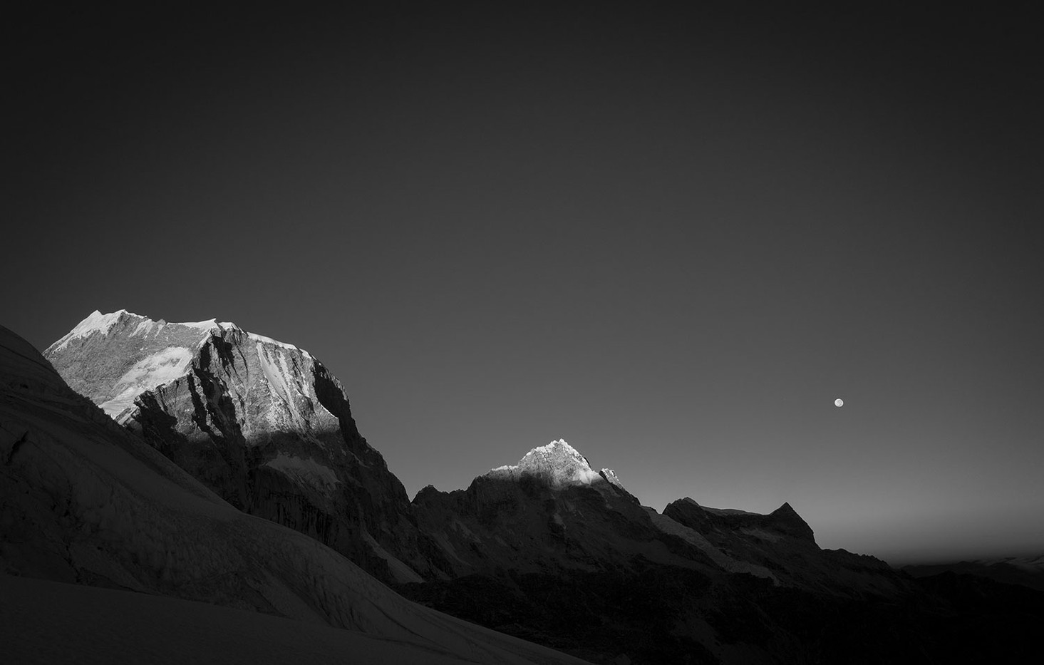 A full moon sets while sunrise strikes the tops of Raranpalca and Oschapalca.