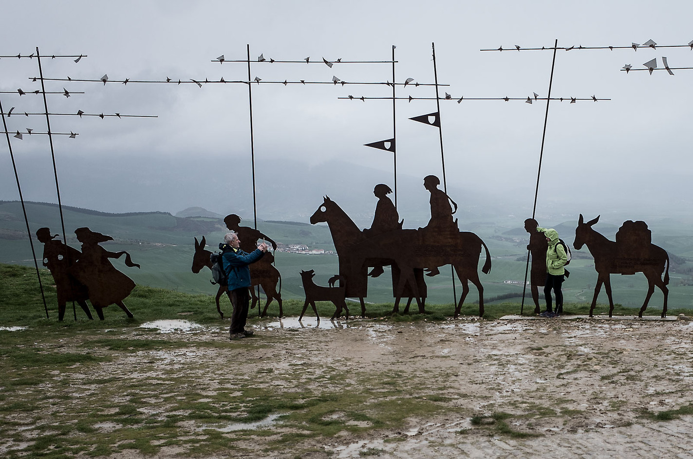 Pilgrims take a photo next to the sculpture atop the minor ridge of Alto de Perdón, a few kilometers outside of Pamplona.