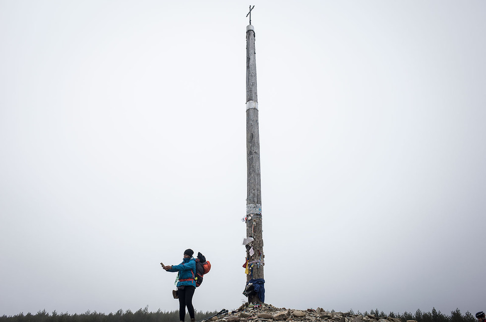 A pilgrim takes a selfie in front of the Cruz del Hierro.