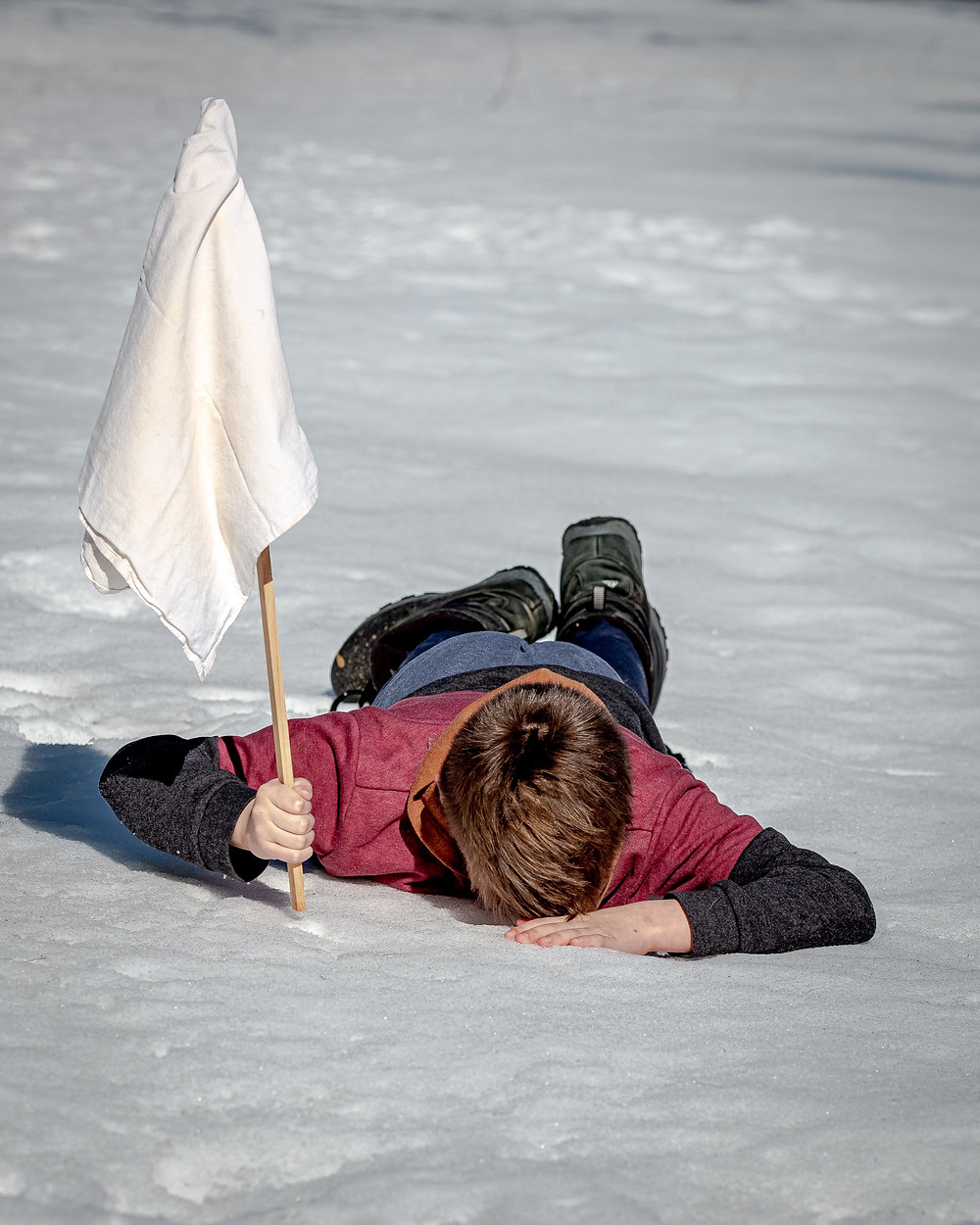 Person lying on snow with a white flag