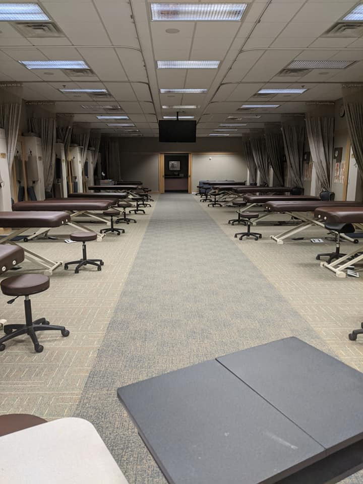 Image: Classroom with a dozen empty massage tables and stools. Teacher's desk in the foreground.