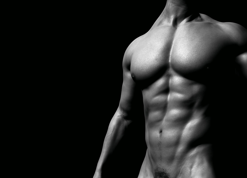 A naked man with six pack abs and chiseled chest