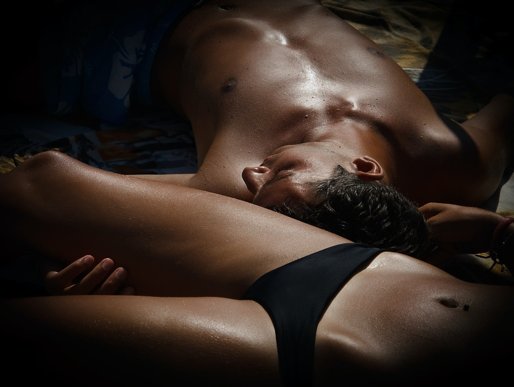A couple laying next to each other in bed