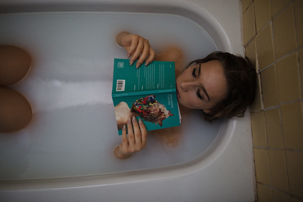 A woman reading an erotic novel in the bath tub