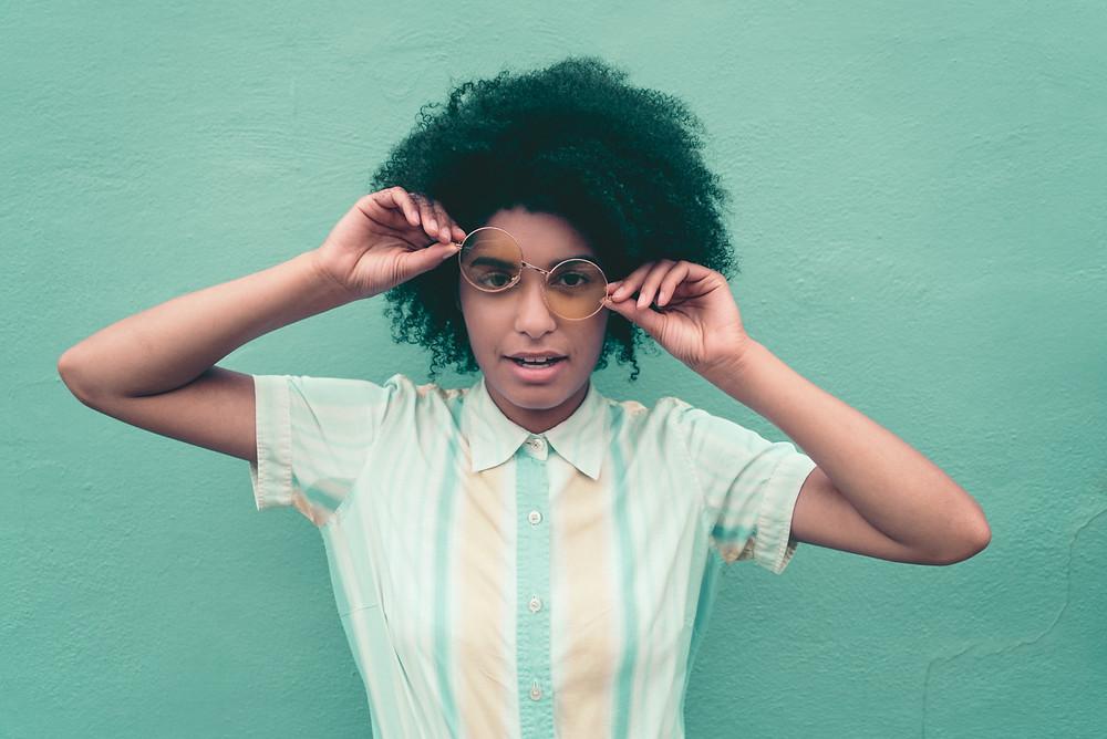 femme moderne tient ses lunettes mur bleu