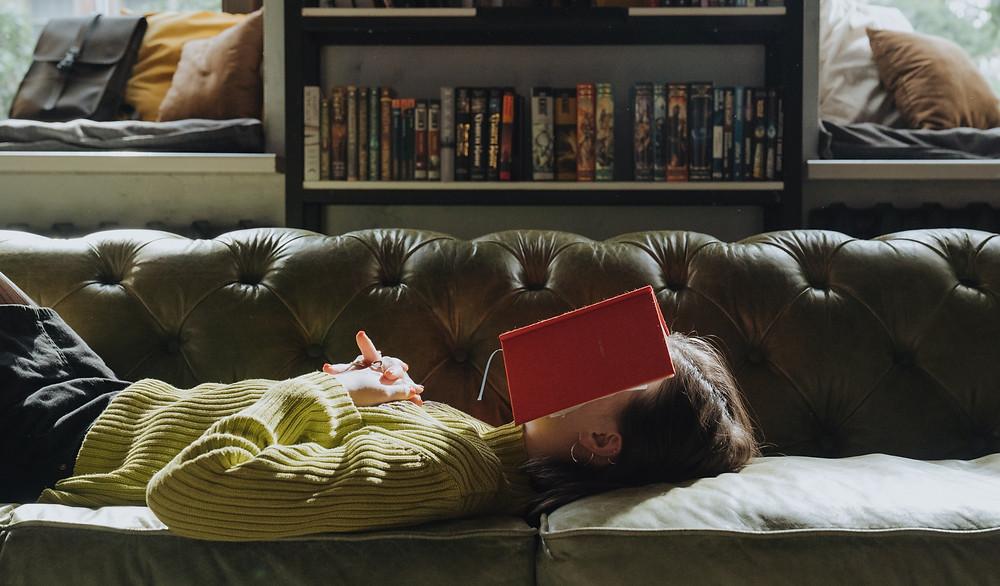 femme allongée sur canapé en train de lire