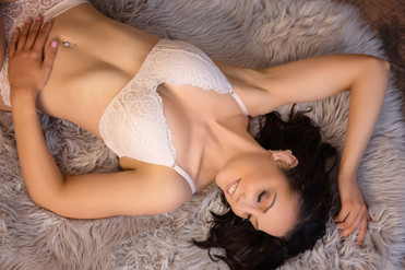 boudoir smile eyes closed laying down top angle