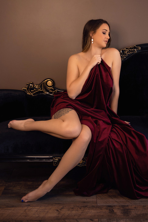 boudoir implied nude on chase covering with red sheet