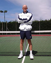 Coach Neil Driver standing in front of a tennis net