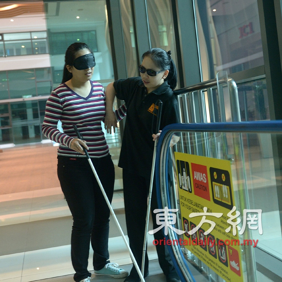 Going down the escalator blindfolded, guided by Michelle.