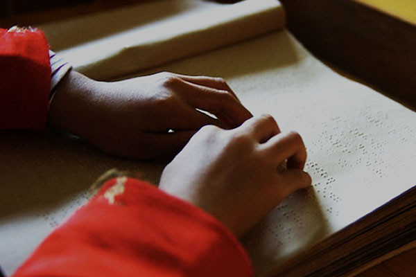 Hands on a book, reading Braille