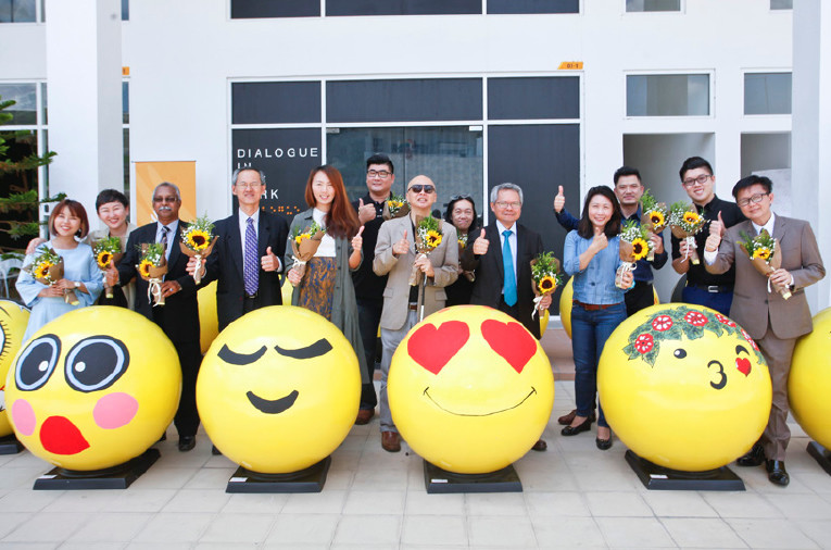 VIPs photographed with drawn emojis during the launch